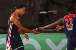 Washington Wizards guard Jerome Robinson, left, celebrates after making a basket during the third quarter of an NBA basketball game against the New Orleans Pelicans, Friday, Aug. 7, 2020, in Lake Buena Vista, Fla. (Kim Klement/Pool Photo via AP)