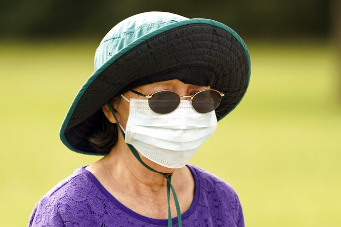 A women wears a mask while walking in a park Wednesday, July 1, 2014, in Houston. Harris County Commissioners have voted to extend the recently-issued mask order until August 26. The order directs any businesses providing goods or services to require all employees and visitors to wear face coverings in areas of close proximity to co-workers or the public. (AP Photo/David J. Phillip)