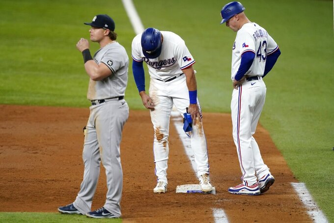 New York Yankees first baseman Luke Voit, left, stands by as Texas Rangers first base coach Corey Ragsdale (43) checks on Joey Gallo, center, in the third inning of a baseball game in Arlington, Texas, Monday, May 17, 2021. Gallo, who earned a walk in the at-bat, stumbled on the bag looking back at the plate landing awkwardly on the ground. Gallo continued playing in the game. (AP Photo/Tony Gutierrez)
