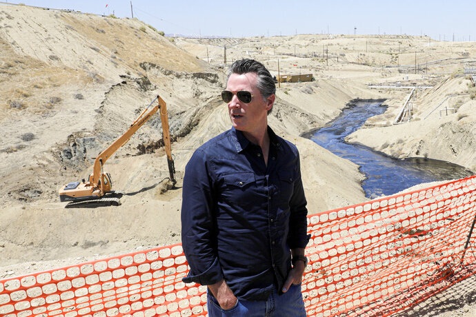 FILE - In this July 24, 2019, file photo, Gov. Gavin Newsom tours the Chevron oil field west of Bakersfield where a spill of more than 800,000 gallons flowed into a dry creek bed in McKittrick, Calif. Newsom's administration has temporarily banned new oil wells in California if they use an extraction method that is linked to an ongoing oil spill in Kern County. On Tuesday, Nov. 19, 2019, the Division of Oil, Gas and Geothermal Resources announced it will not approve new oil wells that use high-pressure steam to soften the thick crude underground so it can flow more easily. (Irfan Khan/Los Angeles Times via AP, Pool, File)