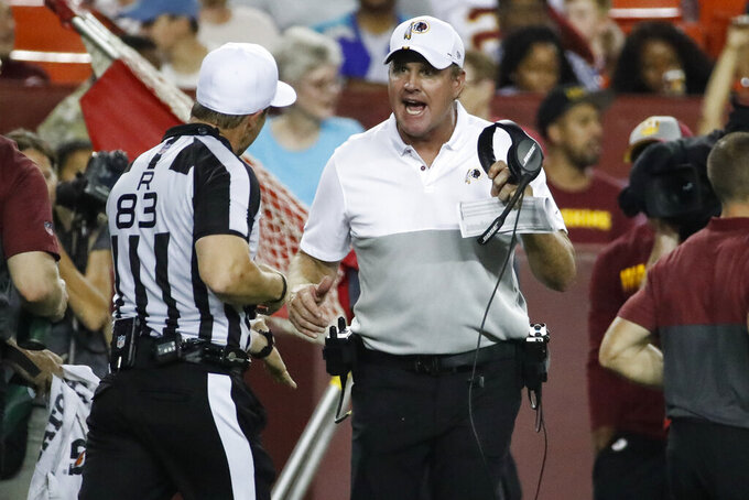 Washington Redskins coach Jay Gruden, center, discusses a call with referee Shawn Hochuli (83) during the second half of the team's NFL preseason football game against the Cincinnati Bengals, Thursday, Aug. 15, 2019, in Landover, Md. The Bengals won 23-13. (AP Photo/Alex Brandon)