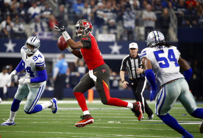 FILE - In this Dec. 23, 2018, file photo, Dallas Cowboys' Randy Gregory (94) and Jaylon Smith (54) pursue as Tampa Bay Buccaneers quarterback Jameis Winston (3) prepares to throw a pass during an NFL football game in Arlington, Texas. Both Cowboys were considered second-round gambles for vastly different reasons--Gregory because of a battle with substance abuse that eventually led to three suspensions, Smith because of a devastating left knee injury in his final college game. With the Cowboys headed to a divisional playoff at the Los Angeles Rams on a team with a defense-first mentality, Gregory and Smith are looking more like second-round payoffs all the time. (AP Photo/Michael Ainsworth, File)
