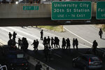 FILE—In this file photo from June 1, 2020, protesters march down Interstate 676 in Philadelphia, during a march calling for justice over the death of George Floyd. Three class-action lawsuits filed in Philadelphia on Tuesday, July 14,  accuse the city of using military-level force against peaceful demonstrators protesting racial inequality and police brutality.  (AP Photo/Matt Rourke, File)