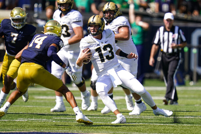Purdue quarterback Jack Plummer (13) scrambles away from Notre Dame safety Kyle Hamilton (14) during the first half of an NCAA college football game in South Bend, Ind., Saturday, Sept. 18, 2021. (AP Photo/Michael Conroy)