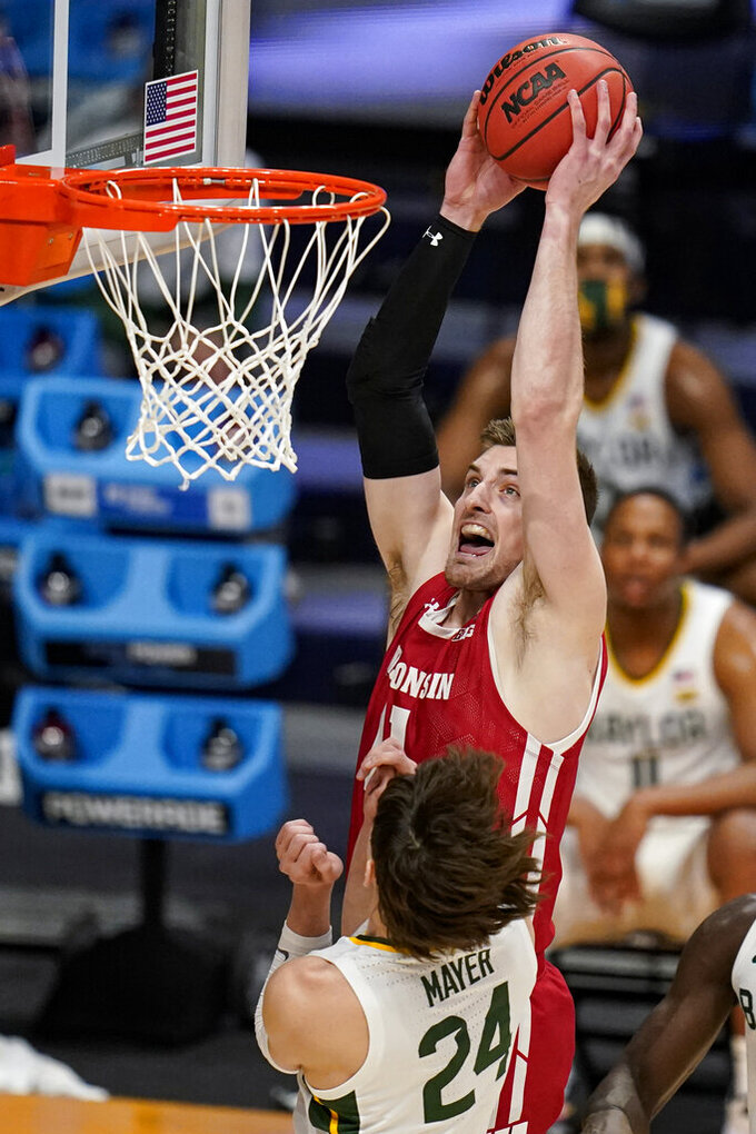Wisconsin forward Micah Potter (11) goes up for a dunk over Baylor guard Matthew Mayer (24) in the first half of a second-round game in the NCAA men's college basketball tournament at Hinkle Fieldhouse in Indianapolis, Sunday, March 21, 2021. (AP Photo/Michael Conroy)
