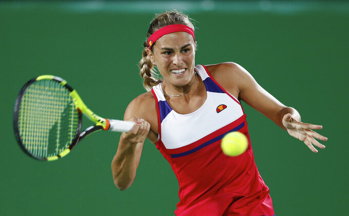 FILE - In this Saturday, Aug. 13, 2016, file photo, Monica Puig, of Puerto Rico, returns to Germany's Angelique Kerber in the gold medal match of the women's tennis competition at the 2016 Summer Olympics in Rio de Janeiro, Brazil. Reigning Olympic tennis gold medalist Puig will miss the Tokyo Games and the rest of the 2021 season after having surgery on her right shoulder. (AP Photo/Vadim Ghirda, File)