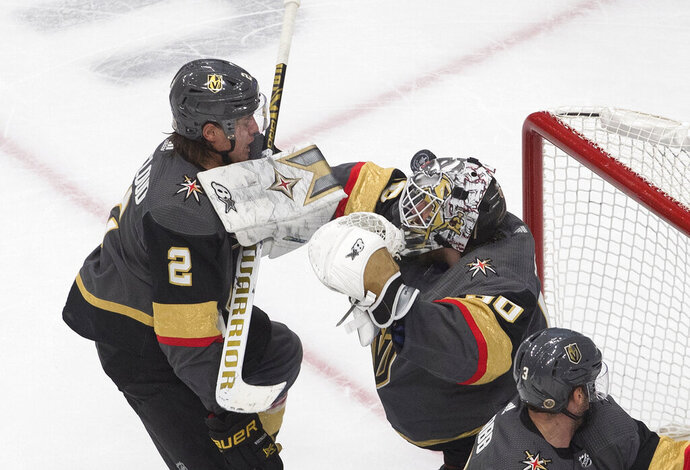 Vegas Golden Knights goalie Robin Lehner (90) makes a save as Zach Whitecloud (2) defends during the third period against the Chicago Blackhawks in Game 1 of an NHL hockey Stanley Cup first-round playoff series, Tuesday, Aug. 11, 2020, in Edmonton, Alberta. (Jason Franson/The Canadian Press via AP)