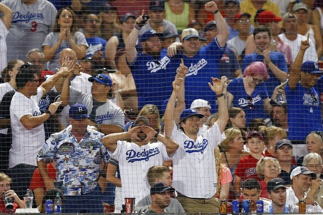 FILE - In this July 13, 2019, file photo, Los Angeles Dodgers fans celebrate a solo home run by Cody Bellinger during the seventh inning of a baseball game against the Boston Red Sox in Boston. Whenever the baseball season begins, Los Angeles Dodgers fans who subscribe to DirecTV and its subsidiaries will have access to the team's regional sports network after a deal ended a nearly seven-year stalemate. (AP Photo/Michael Dwyer, File)