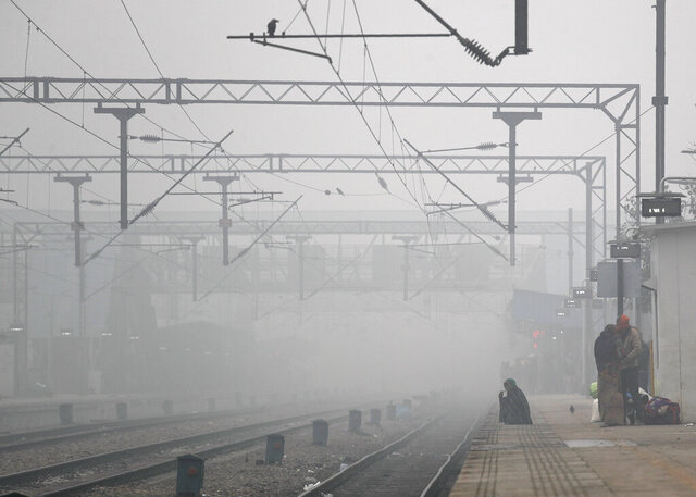Passengers wait for trains in the morning fog in New Delhi, India, Monday, Dec. 30, 2019. The Indian capital which is witnessing the longest spell of cold weather in the last 22 years, woke up to a blanket of dense fog disrupting rail, road and air traffic adversely. (AP Photo/Manish Swarup)