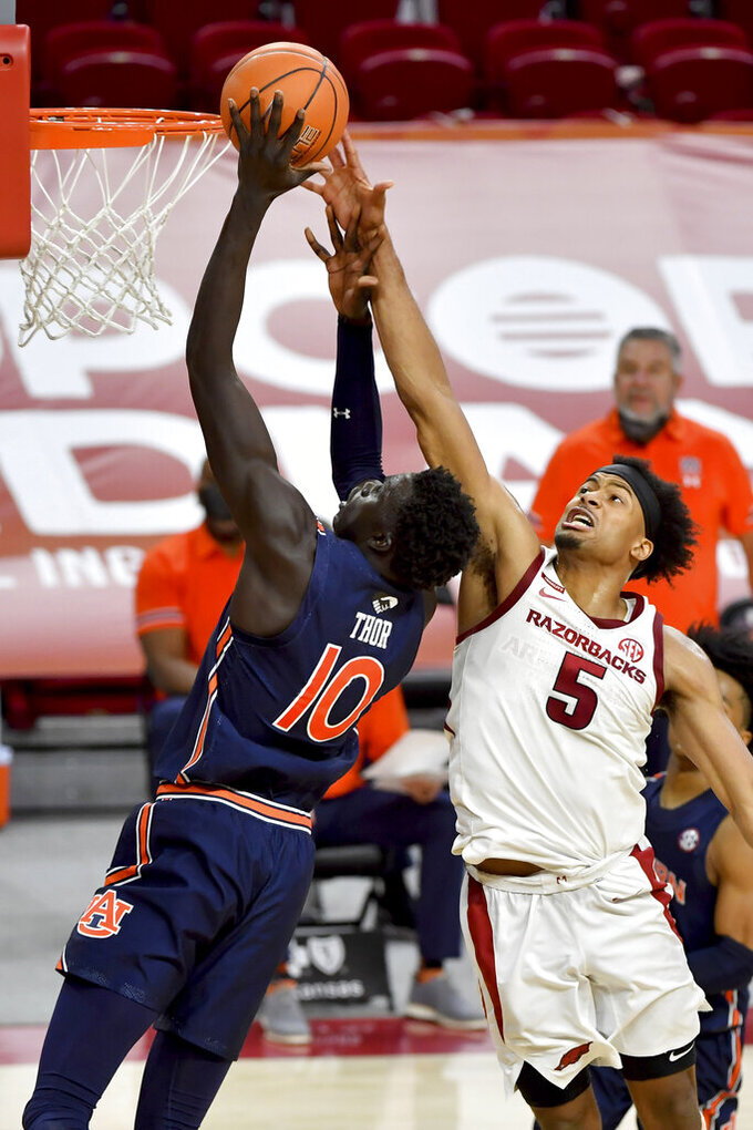 Auburn forward JT Thor (10) tries to shoot over Arkansas defender Moses Moody (5) during the second half of an NCAA college basketball game Wednesday, Jan. 20, 2021, in Fayetteville, Ark. (AP Photo/Michael Woods)