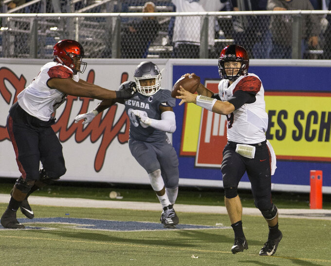San Diego State quarterback Ryan Agnew (9) looks to throw as he is chased by against Nevada's Korey Rush (90) in the second half of an NCAA college football game in Reno, Nev., Saturday, Oct. 27, 2018. (AP Photo/Tom R. Smedes)
