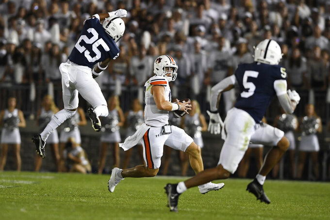 Auburn quarterback Bo Nix (10) looks to elude Penn State defenders Daequan Hardy (25) and Tariq Castro-Fields (5) during an NCAA college football game against Auburn in State College, Pa., on Saturday, Sept. 18, 2021. (AP Photo/Barry Reeger)
