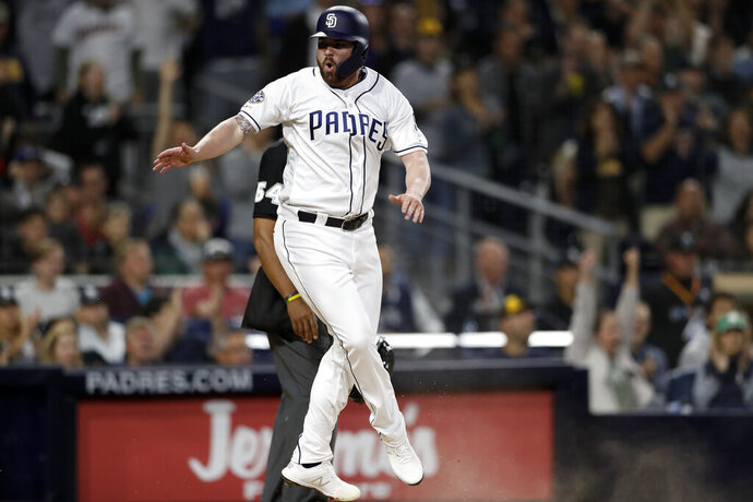 San Diego Padres' Logan Allen reacts after scoring on a throwing error by Milwaukee Brewers third baseman Mike Moustakas after San Diego Padres' Eric Hosmer lined out during the fifth inning of a baseball game Tuesday, June 18, 2019, in San Diego. (AP Photo/Gregory Bull)