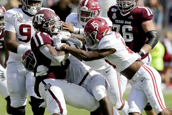 Texas A&M running back Isaiah Spiller (28) is wrapped up by the Alabama defense after a short gain during the first half of an NCAA college football game, Saturday, Oct. 12, 2019, in College Station, Texas. (AP Photo/Sam Craft)