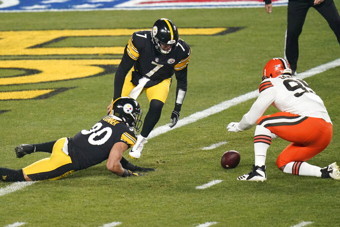 Pittsburgh Steelers quarterback Ben Roethlisberger (7), James Conner (30) and Cleveland Browns defensive end Myles Garrett (95) attempt to recover a fumbled high snap during the first half of an NFL wild-card playoff football game, Sunday, Jan. 10, 2021, in Pittsburgh. Cleveland Browns strong safety Karl Joseph (42) recovered the ball in the end zone for a touchdown. (AP Photo/Keith Srakocic)
