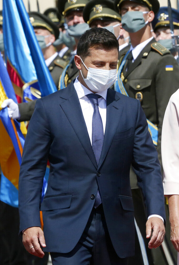 FILE - In this file photo dated Tuesday, July. 21, 2020, Ukrainian President Volodymyr Zelenskiy reviews the honor guard during a welcome ceremony in Kyiv, Ukraine. It is announced Monday Nov. 9, 2020, that Volodymyr Zelenskiy has tested positive for the COVID-19 coronavirus.(AP Photo/Efrem Lukatsky, FILE)