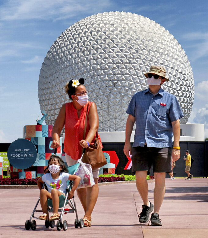 Guests arrive to attend the official re-opening day of Epcot at Walt Disney World in Lake Buena Vista, Fla., Wednesday, July 15, 2020. All four of Disney's Florida parks are now open, including Hollywood Studios, the Magic Kingdom and Animal Kingdom, with limited capacity and safety protocols in place in response to the coronavirus pandemic.  (Joe Burbank/Orlando Sentinel via AP)