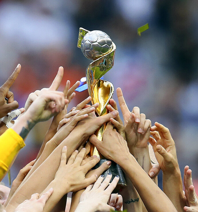 FILE - In this July 7, 2019, file photo, U.S. players hold the trophy as they celebrate their victory in the Women's World Cup soccer final in Decines, outside Lyon, France. FIFA's Council has unanimously approved expanding the Women's World Cup from 24 teams to 32 for 2023 and has reopened bidding to host the tournament but made no mention of changing prize money. FIFA said Wednesday, July 31, 2019, the decision was made remotely. (AP Photo/David Vincent, File)