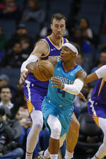 Charlotte Hornets guard Devonte' Graham (4) passes as Phoenix Suns forward Frank Kaminsky, rear, defends in the first half of an NBA basketball game in Charlotte, N.C., Monday, Dec. 2, 2019. (AP Photo/Nell Redmond)