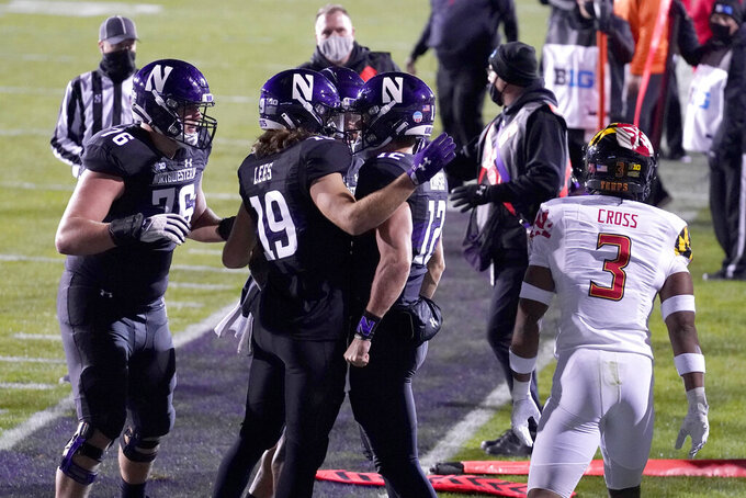 Northwestern quarterback Peyton Ramsey (12) celebrates with teammates after scoring a touchdown during the first half of an NCAA college football game against Maryland in Evanston, Ill., Saturday, Oct. 24, 2020. (AP Photo/Nam Y. Huh)
