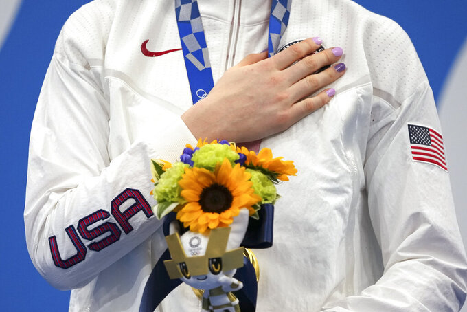Gold medalist Lydia Jacoby of the United States stands on the podium after receiving her gold medal in the final of the women's 100-meter breaststroke at the 2020 Summer Olympics, Tuesday, July 27, 2021, in Tokyo, Japan. (AP Photo/Matthias Schrader)