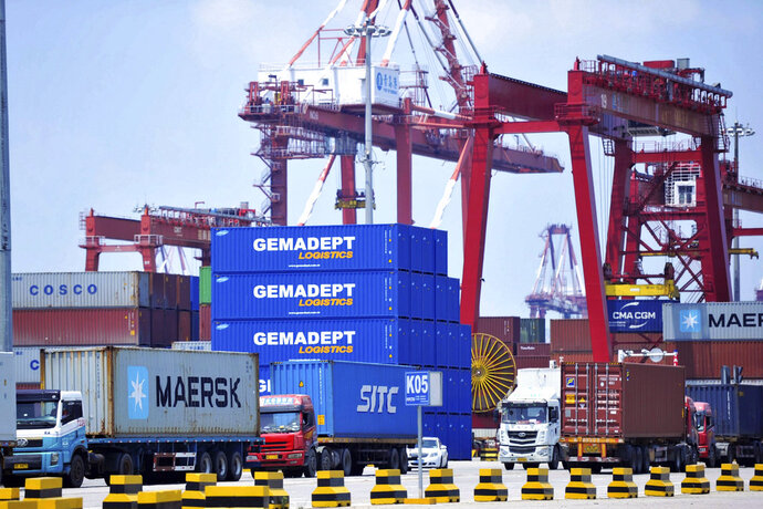 FILE - In this July 6, 2018, file photo, trucks haul containers from a container port in Qingdao in eastern China's Shandong province. China's trade grew by double digits in June despite mounting tensions with Washington but the government warned it will face