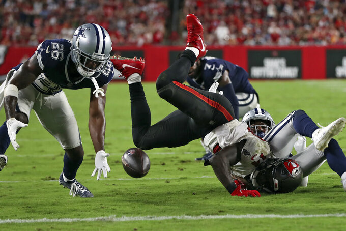 Dallas Cowboys cornerback Jourdan Lewis (26) picks up a fumble by Tampa Bay Buccaneers wide receiver Chris Godwin (14) during the second half of an NFL football game Thursday, Sept. 9, 2021, in Tampa, Fla. (AP Photo/Mark LoMoglio)