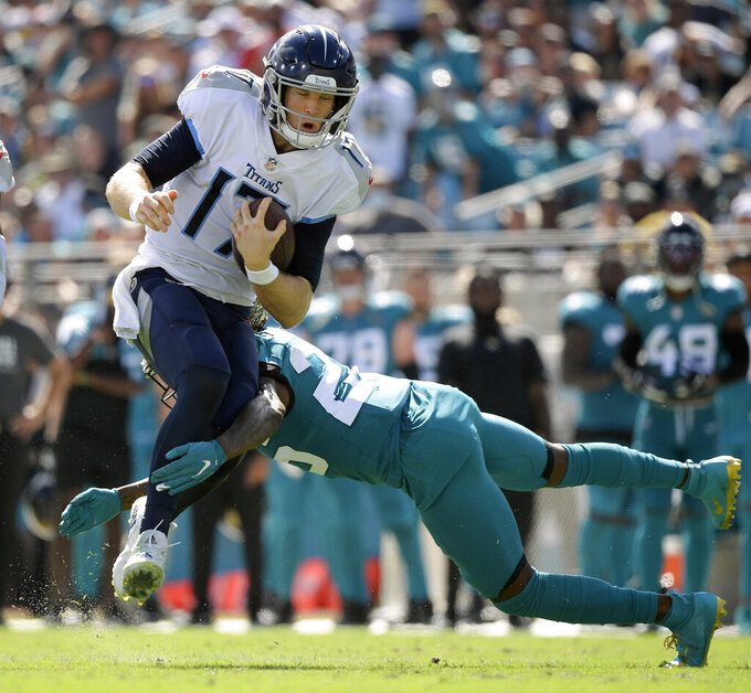 Tennessee Titans quarterback Ryan Tannehill, left, tries to hurdle over Jacksonville Jaguars cornerback Shaquill Griffin during the second half of an NFL football game, Sunday, Oct. 10, 2021, in Jacksonville, Fla. (AP Photo/Phelan M. Ebenhack)