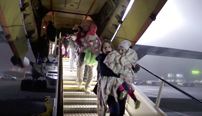 In grab of video provided by Russian Emergency Situations Ministry on Tuesday, Nov. 19, 2019, Russian officials carry children after Emergency Situations Ministry's airplane landed on Monday night at Zhukovsky airport outside Moscow, Russia. Russia says it has repatriated another 32 children of members of the Islamic State group from Iraq. (Russian Ministry for Emergency Situations photo via AP)