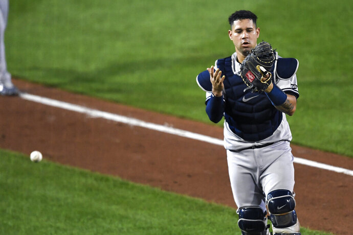 New York Yankees catcher Gary Sánchez looks at his glove after dropping a foul hit by Toronto Blue Jays' Cavan Biggio during the fifth inning of a baseball game in Buffalo, N.Y., Tuesday, Sept. 8, 2020. (AP Photo/Adrian Kraus)