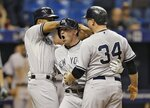 FILE - In this Monday, Sept. 14, 2015, file photo, New York Yankees' Slade Heathcott, center, celebrates his three-run home run off Tampa Bay Rays relief pitcher Brad Boxberger with Chris Young, left, and Brian McCann during the ninth inning of a baseball game  in St. Petersburg, Fla. Heathcott is on the staff of More Than Baseball, an organization that aims to address the inequity of minor league baseball's pay system. (AP Photo/Chris O'Meara, File)