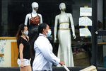 FILE - In this Sept. 29, 2020, file photo, women walk past mannequins wearing face masks advertised for sale, at a shop in Makati city, Philippines. Developing economies in Asia will likely grow at a slower pace than earlier expected due to prolonged COVID-19 outbreaks and uneven progress in vaccinations, the Asian Development Bank said in a report Wednesday, Sept. 22, 2021.(AP Photo/Aaron Favila, File)