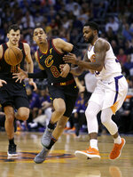 Cleveland Cavaliers guard Jordan Clarkson (8) drives on Phoenix Suns guard Troy Daniels in the first half during an NBA basketball game, Tuesday, March 13, 2018, in Phoenix. (AP Photo/Rick Scuteri)