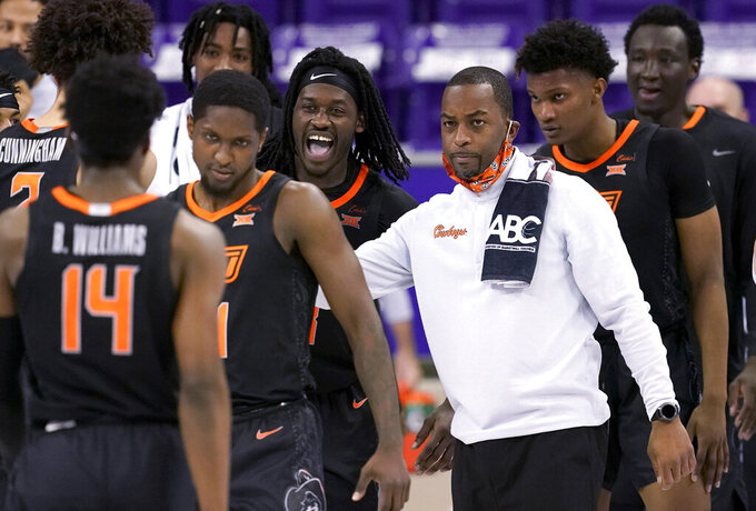 Oklahoma State coach Mike Boynton, right, greets Bryce Williams (14) and others off the court during a timeout in the first half of an NCAA college basketball game against TCU in Fort Worth, Texas, Wednesday, Feb. 3, 2021. (AP Photo/Tony Gutierrez)