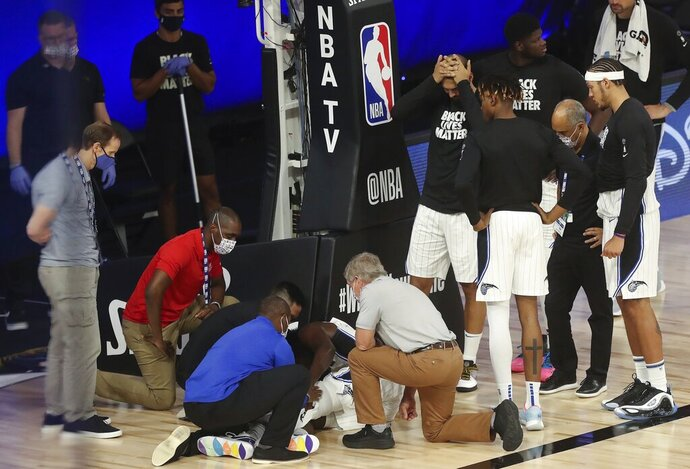 Orlando Magic players surround forward Jonathan Isaac, who receives medical attention after an injuring during the fourth quarter of the team's NBA basketball game against the Sacramento Kings on Sunday, Aug. 2, 2020, in Lake Buena Vista, Fla. (Charles King/Orlando Sentinel via AP)