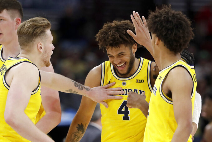 Michigan's Isaiah Livers (4) is congratulated why his teammates after a dunk shot during the first half of an NCAA college basketball game against Minnesota in the semifinals of the Big Ten Conference tournament, Saturday, March 16, 2019, in Chicago. (AP Photo/Nam Y. Huh)