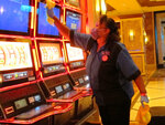 In this July 1, 2020 photo, Jeorganna Barnes, a worker at Harrah's casino in Atlantic City, N.J., wipes slot machines with disinfectant as the casino prepared to reopen after 3 1/2 months of being shut down due to the coronavirus. On Nov. 23, 2020, New Jersey gambling regulators released figures showing Atlantic City's casinos saw their gross operating profits decline by 37% in the third quarter of 2020 as they reopened under restrictions designed to slow the spread of the virus. (AP Photo/Wayne Parry)