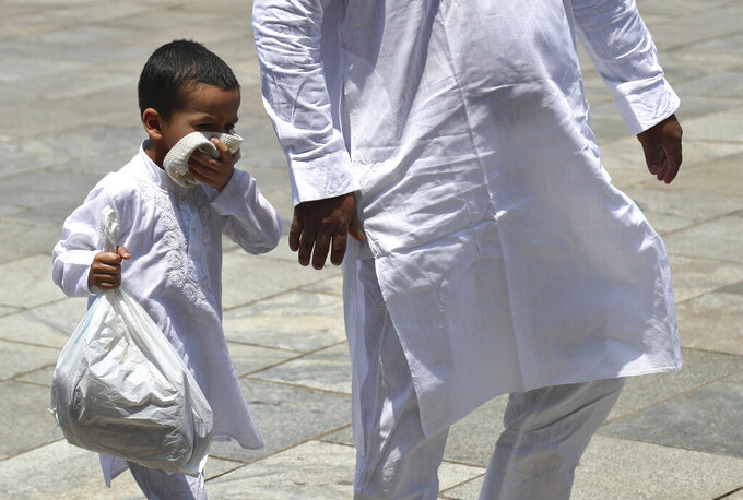 A Muslim boy covers his face with his skull cap as a precaution against the coronavirus as he arrives with a family member to offer last Friday prayers of Ramadan at Mecca Masjid in Hyderabad, India, Friday, May 7, 2021. Indian Prime Minister Narendra Modi faced growing pressure Friday to impose a strict nationwide lockdown, despite the economic pain it will exact, as a startling surge in coronavirus cases that has pummeled the country's health system shows no signs of abating.  (AP Photo /Mahesh Kumar A.)