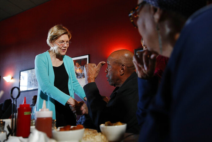 Democratic presidential candidate Sen. Elizabeth Warren, D-Mass., speaks with Bill Mamgum, center, and Shirley Mamgum at EllaEm's Soul Food, Thursday, Feb. 20, 2020, in North Las Vegas, Nev. (AP Photo/John Locher)