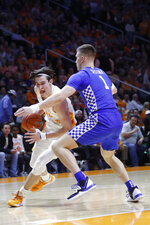 Tennessee forward John Fulkerson (10) drives against Kentucky forward Nate Sestina (1) during the first half of an NCAA college basketball game Saturday, Feb. 8, 2020, in Knoxville, Tenn. (AP Photo/Wade Payne)