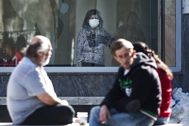 A woman wearing a face mask stands behind a window at AHEPA hospital in the northern port city of Thessaloniki, Greece, Wednesday, Feb. 26, 2020. Greek authorities have confirmed the country's first case of the new conronavirus. The health ministry's head of infectious diseases, Sotiris Tsiodras, said the case was a 38-year-old woman in Thessaloniki who had recently traveled to northern Italy. (AP Photo/Giannis Papanikos)