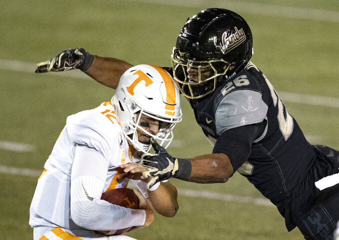 Tennessee quarterback J.T. Shrout (12) is sacked by Vanderbilt linebacker Anfernee Orji (26) during the second half of an NCAA college football game Saturday, Dec. 12, 2020, in Nashville, Tenn. (AP Photo/Wade Payne)