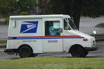 U.S. Postal Service carrier John Graham drives a 28-year-old delivery truck while making's rounds, Wednesday, July 14, 2021, in Portland, Maine. Hundreds of the aging trucks were reported to catch fire in recent years. (AP Photo/Robert F. Bukaty)