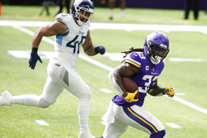 Minnesota Vikings running back Dalvin Cook runs from Tennessee Titans outside linebacker Kamalei Correa (40) during a 39-yard touchdown run in the first half of an NFL football game, Sunday, Sept. 27, 2020, in Minneapolis. (AP Photo/Bruce Kluckhohn)