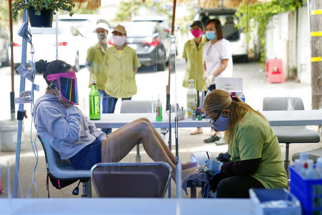 FILE - In this July 22, 2020, file photo, Tyson Salomon, left, gets a pedicure outside Pampered Hands nail salon in Los Angeles. A steady drop in coronavirus cases across California cleared the way Tuesday, Sept. 22, 2020, for the wider reopening of businesses in nine counties, including much of the San Francisco Bay Area, the state's top health official said. Dr. Mark Ghaly, the state health secretary, said nail salons could also reopen with restrictions, though he cautioned that California's reopening must remain