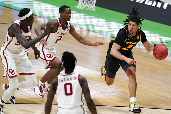 Missouri guard Drew Buggs, right, drives up court ahead of Oklahoma forward Kur Kuath, left, guard Umoja Gibson, center, and forward Victor Iwuakor (0) during the second half of a first-round game in the NCAA men's college basketball tournament at Lucas Oil Stadium, Saturday, March 20, 2021, in Indianapolis. (AP Photo/Darron Cummings)
