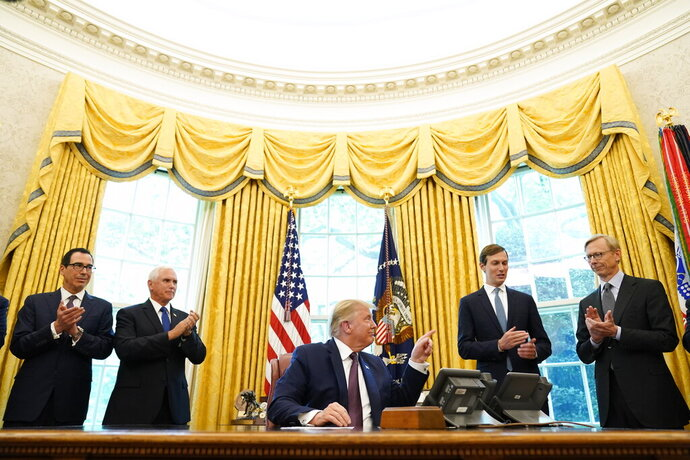 President Donald Trump speaks in the Oval Office of the White House on Friday, Sept. 11, 2020, in Washington. Bahrain has become the latest Arab nation to agree to normalize ties with Israel as part of a broader diplomatic push by Trump and his administration to fully integrate the Jewish state into the Middle East. From left, Treasury Secretary Steven Mnuchin, Vice President Mike Pence, Trump, Jared Kushner and U.S. special envoy for Iran Brian Hook. (AP Photo/Andrew Harnik)