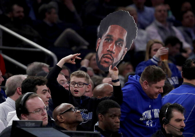A boy holds a photo with the likeness of Seton Hall guard Myles Powell during the first half of an NCAA college basketball game between Seton Hall and Georgetown in the Big East men's tournament, Thursday, March 14, 2019, in New York. (AP Photo/Julio Cortez)