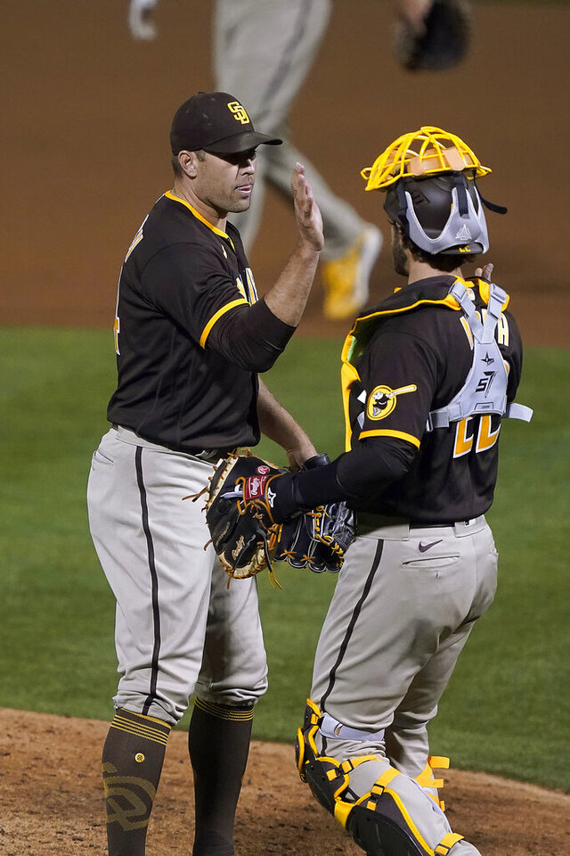 San Diego Padres relief pitcher Craig Stammen, left, is congratulated by catcher Austin Nola after the team's 7-0 victory over the Oakland Athletics in baseball game in Oakland, Calif., Friday, Sept. 4, 2020. (AP Photo/Tony Avelar)