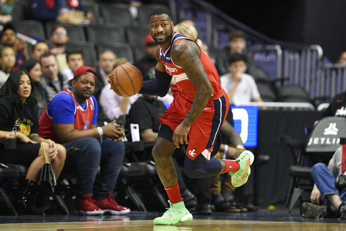 "FILE - In this Dec. 1, 2018, file photo, Washington Wizards guard John Wall (2) dribbles the ball during the first half of an NBA basketball game against the Brooklyn Nets in Washington. Wizards point guard John Wall says he is ""110%"" healthy after missing the past 1½ years with two major injuries. He is working out at home and looking forward to getting back to the NBA next season.(AP Photo/Nick Wass, File)"